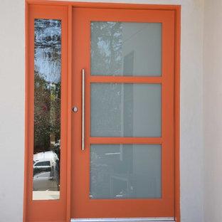 Inredning av en modern mellanstor ingång och ytterdörr, med vita väggar, betonggolv, en enkeldörr och en orange dörr