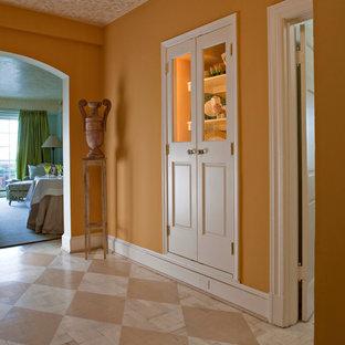 На фото: фойе среднего размера в стиле современная классика с оранжевыми стенами и деревянным полом