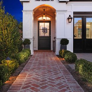 Entryway - traditional entryway idea in Orange County with white walls and a black front door