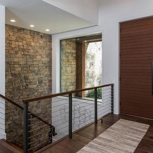 他の地域の中くらいの回転式ドアラスティックスタイルのおしゃれな玄関ロビー (白い壁、濃色無垢フローリング、濃色木目調のドア、茶色い床) の写真
