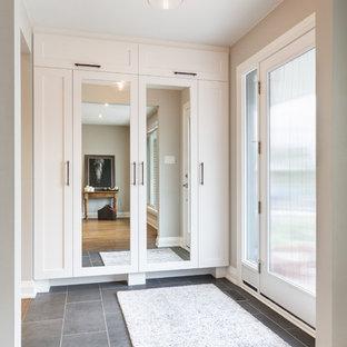 Modelo de distribuidor tradicional renovado, de tamaño medio, con paredes grises, puerta simple, puerta de vidrio y suelo de pizarra