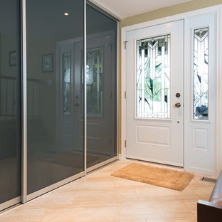 Inspiration for a mid-sized contemporary travertine floor entryway remodel in Ottawa with beige walls and a white front door