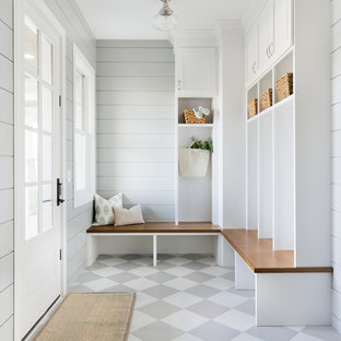 Immagine di un grande ingresso con anticamera costiero con pareti grigie, pavimento con piastrelle in ceramica, una porta singola, una porta bianca e pavimento grigio