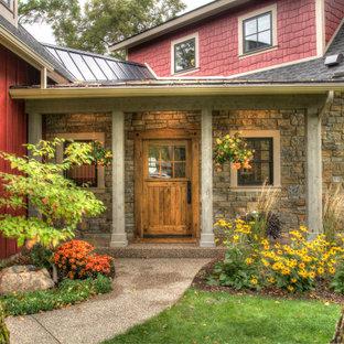 Idee per una grande porta d'ingresso country con pareti rosse, pavimento in cemento, una porta singola, una porta in legno bruno e pavimento grigio