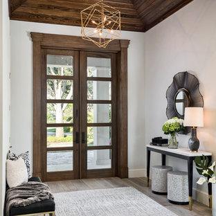 Inspiration pour un hall d'entrée traditionnel avec un mur blanc, une porte double, une porte en bois foncé, un sol gris et un sol en bois clair.