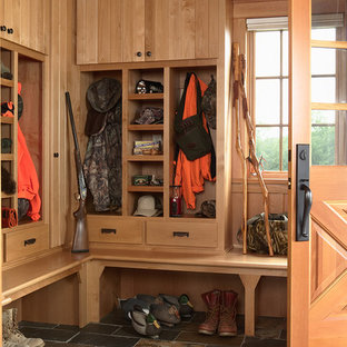 Example of a mountain style slate floor mudroom design in Minneapolis with a medium wood front door