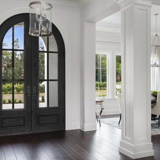 Стильный дизайн: большое фойе в средиземноморском стиле с серыми стенами, темным паркетным полом, двустворчатой входной дверью, металлической входной дверью и правильным освещением - последний тренд