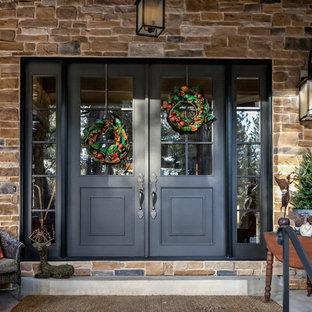 Réalisation d'une grand porte d'entrée tradition avec un mur beige, une porte double et une porte noire.