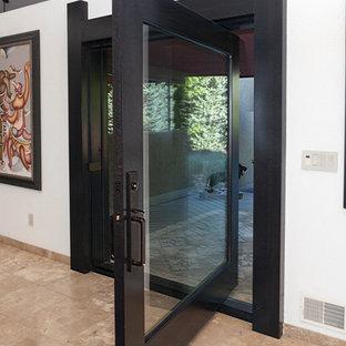 デンバーの大きい回転式ドアモダンスタイルのおしゃれな玄関ドア (白い壁、トラバーチンの床、ガラスドア、ベージュの床) の写真
