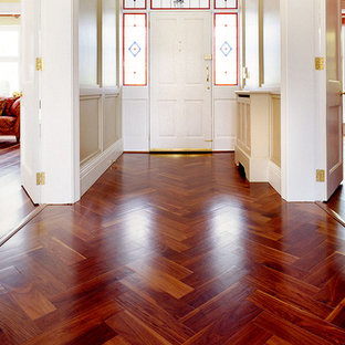 Inspiration for a mid-sized timeless medium tone wood floor entryway remodel in New York with beige walls and a white front door