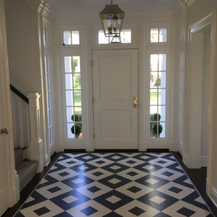 Mid-sized elegant ceramic floor and blue floor entryway photo in Orange County with white walls and a white front door