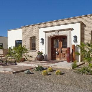 Réalisation d'une porte d'entrée sud-ouest américain de taille moyenne avec un mur beige, une porte double et une porte en bois brun.