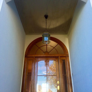 Entryway - large traditional entryway idea in New Orleans with a medium wood front door