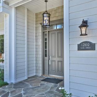 デトロイトの中くらいの片開きドアトラディショナルスタイルのおしゃれな玄関ドア (グレーの壁、グレーのドア) の写真