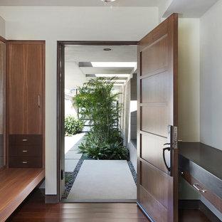 Exemple d'une grand porte d'entrée rétro avec un sol en bambou, une porte simple et une porte en bois brun.