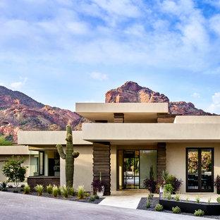 Aménagement d'une grand porte d'entrée sud-ouest américain avec un mur beige, une porte pivot, une porte en verre et un sol beige.