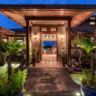 Example of a large island style front door design in Hawaii with a dark wood front door