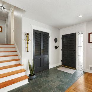 Inredning av en klassisk liten ingång och ytterdörr, med vita väggar, skiffergolv, en enkeldörr, en svart dörr och grönt golv