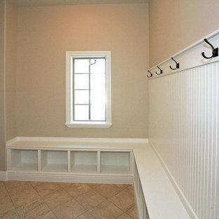 Bild på ett stort vintage kapprum, med beige väggar, travertin golv, en enkeldörr och en vit dörr