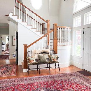 Foto di un ingresso boho chic con pareti bianche, pavimento in legno massello medio, una porta singola, una porta bianca e pavimento marrone