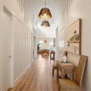 Foto de hall marinero, grande, con paredes blancas, suelo laminado, puerta doble, puerta blanca y suelo marrón