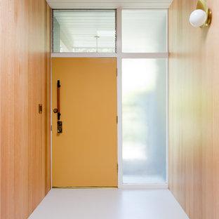 Foto på en 60 tals hall, med bruna väggar, en enkeldörr, en orange dörr och vitt golv