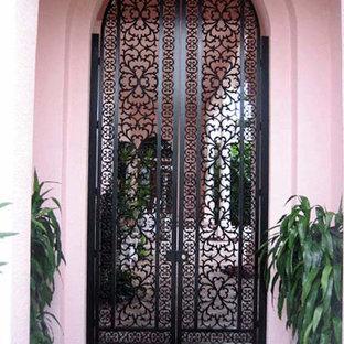 マイアミの中くらいの両開きドア地中海スタイルのおしゃれな玄関ドア (ピンクの壁、セラミックタイルの床、黒いドア、ベージュの床) の写真