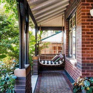 Inspiration pour une entrée craftsman avec un mur marron, un sol en carrelage de céramique, une porte simple, une porte noire et un sol multicolore.