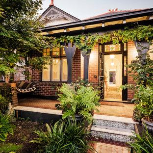シドニーの中サイズの片開きドアコンテンポラリースタイルのおしゃれな玄関 (茶色い壁、セラミックタイルの床、黒いドア、マルチカラーの床) の写真