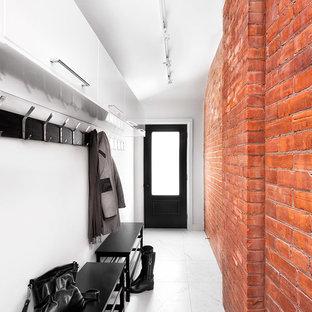 Industriell inredning av en entré, med vita väggar och en enkeldörr