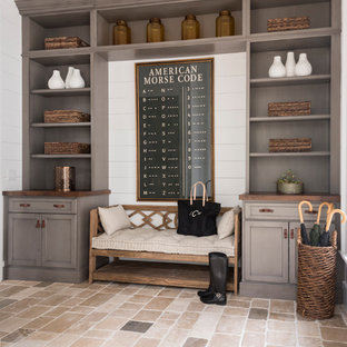 Inspiration for a coastal beige floor mudroom remodel in Other with white walls