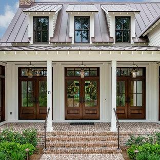 Lantlig inredning av en stor ingång och ytterdörr, med vita väggar, en dubbeldörr och mörk trädörr