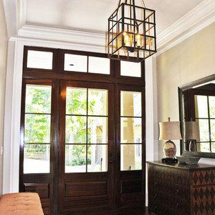 Diseño de distribuidor clásico, de tamaño medio, con paredes beige, suelo de madera oscura, puerta simple y puerta de vidrio