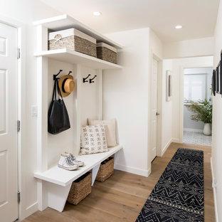 Exemple d'une entrée chic de taille moyenne avec un vestiaire, un mur blanc et un sol en bois clair.