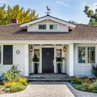 ロサンゼルスの中サイズの片開きドアカントリー風おしゃれな玄関ドア (黒いドア、白い壁、ライムストーンの床) の写真