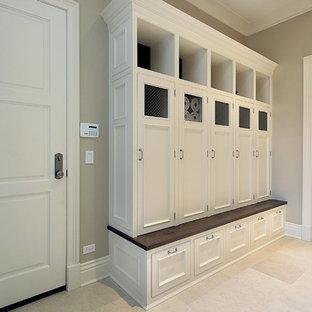 クリーブランドの中くらいの片開きドアトランジショナルスタイルのおしゃれなマッドルーム (ライムストーンの床、グレーの壁、白いドア、ベージュの床) の写真
