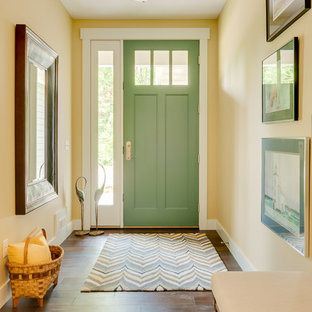 Mid-sized arts and crafts medium tone wood floor entryway photo in Grand Rapids with yellow walls and a green front door