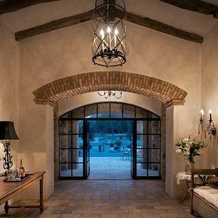 Double front door - large southwestern double front door idea in Phoenix with beige walls and a glass front door