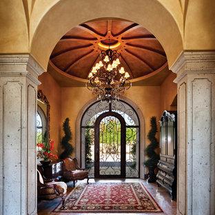 Inspiration för stora klassiska foajéer, med beige väggar, travertin golv, en enkeldörr och metalldörr