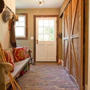 Ejemplo de vestíbulo posterior de estilo de casa de campo con suelo de ladrillo, puerta simple, puerta blanca, paredes beige y suelo rojo