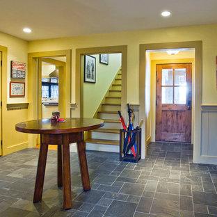 ソルトレイクシティの広い片開きドアおしゃれな玄関ロビー (黄色い壁、スレートの床、濃色木目調のドア) の写真