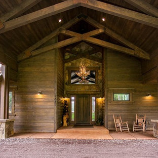 Inspiration for a mid-sized craftsman concrete floor and orange floor front door remodel in Other with brown walls and a medium wood front door