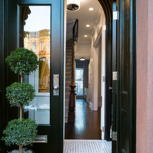 Large transitional marble floor entryway photo in New York with white walls and a black front door