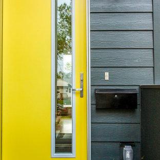 Неиссякаемый источник вдохновения для домашнего уюта: маленькая входная дверь в современном стиле с серыми стенами, полом из фанеры, одностворчатой входной дверью и желтой входной дверью
