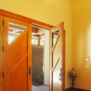 Esempio di una porta d'ingresso di medie dimensioni con pareti gialle, pavimento in terracotta, una porta a due ante, una porta in legno bruno e pavimento marrone