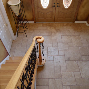 Example of a classic travertine floor entryway design in Tampa with a medium wood front door