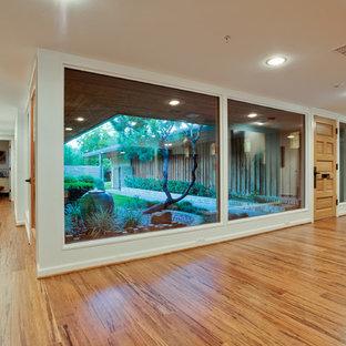 Retro inredning av en entré, med vita väggar, bambugolv, en enkeldörr och ljus trädörr