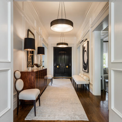 Example of a mid-sized transitional medium tone wood floor and brown floor entryway design in Other with white walls and a black front door