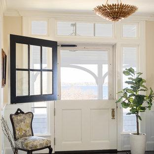 Exemple d'une porte d'entrée bord de mer avec une porte hollandaise, un mur beige, un sol en bois foncé et une porte blanche.