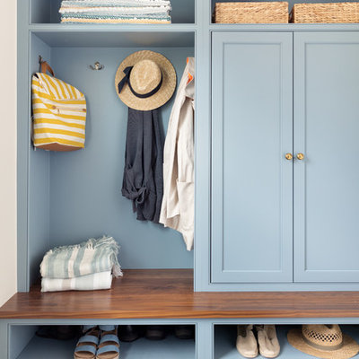 Inspiration for a coastal dark wood floor mudroom remodel in Boston with blue walls
